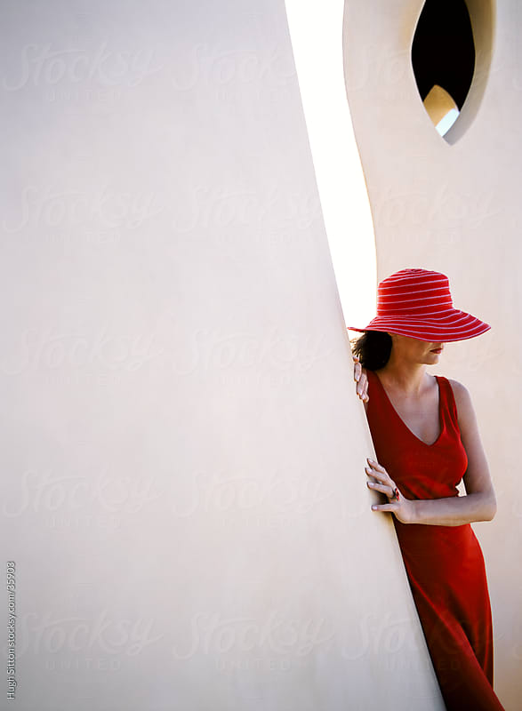 Woman in red dress and red hat  standing against white wall. by Hugh Sitton for Stocksy United