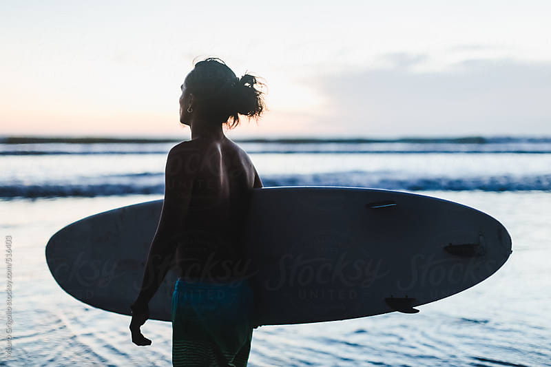 Surfer on the beach at sunset by Mauro Grigollo for Stocksy United