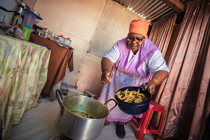 African domestic worker woman cooking by Micky Wiswedel for Stocksy United