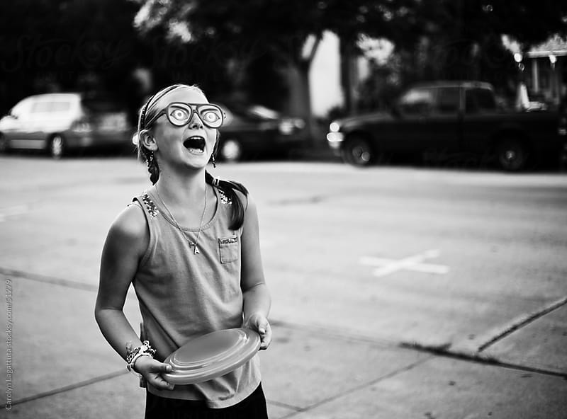 Young girl wearing crazy glasses, holding a frisbee and laughing by Carolyn Lagattuta for Stocksy United