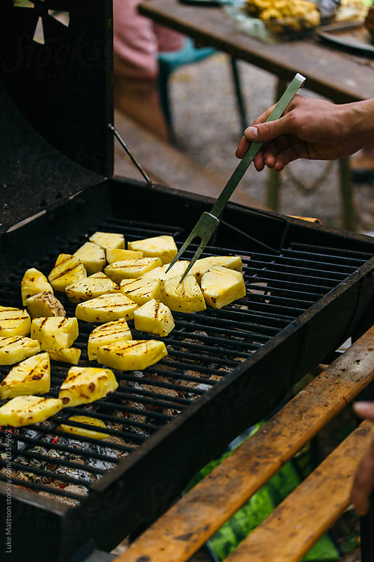 Man Tending To Sliced Pineapple Cooking Over BBQ by Luke Mattson for Stocksy United