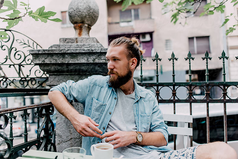 Portrait of a young bearded man in a cafe by Boris Jovanovic for Stocksy United