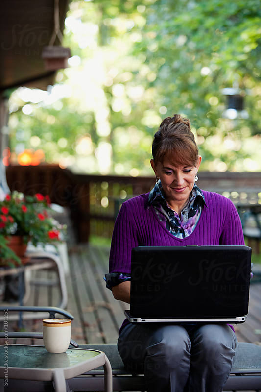 Working: Woman Doing Business From Outdoor Deck by Sean Locke for Stocksy United