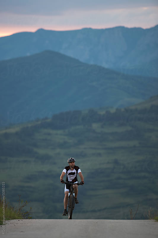 Young man cyclist riding alone on the road  by RG&B Images for Stocksy United