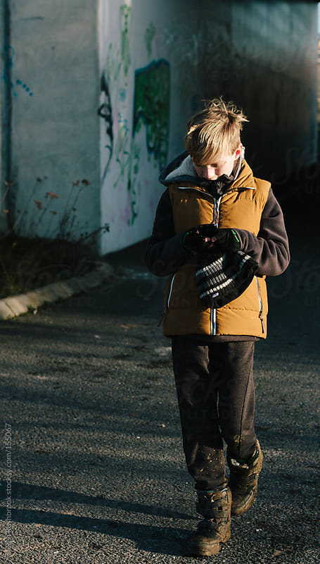a boy walking and texting. by Helen Rushbrook for Stocksy United
