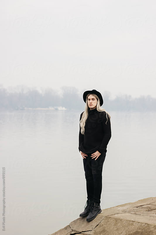 Male model with black hat and long hair standing near river by Evil Pixels Photography for Stocksy United