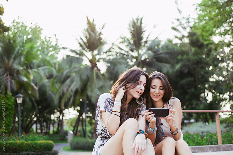 Friendship - friends looking at the phone and giggling  by Jovo Jovanovic for Stocksy United