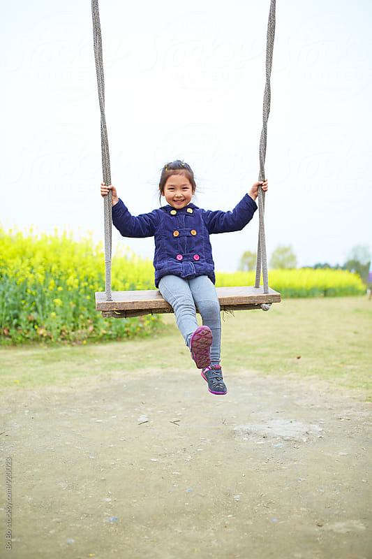 happy little girl playing on the swing by Bo Bo for Stocksy United