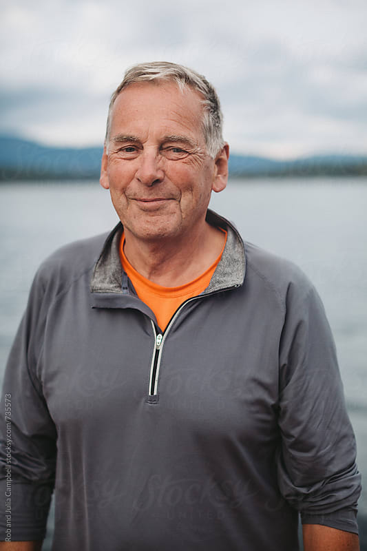 Portrait of older man smiling near water by Rob and Julia Campbell for Stocksy United