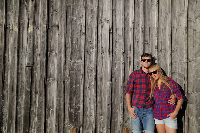 young couple in love leaning wall sun glasses by rolfo for Stocksy United