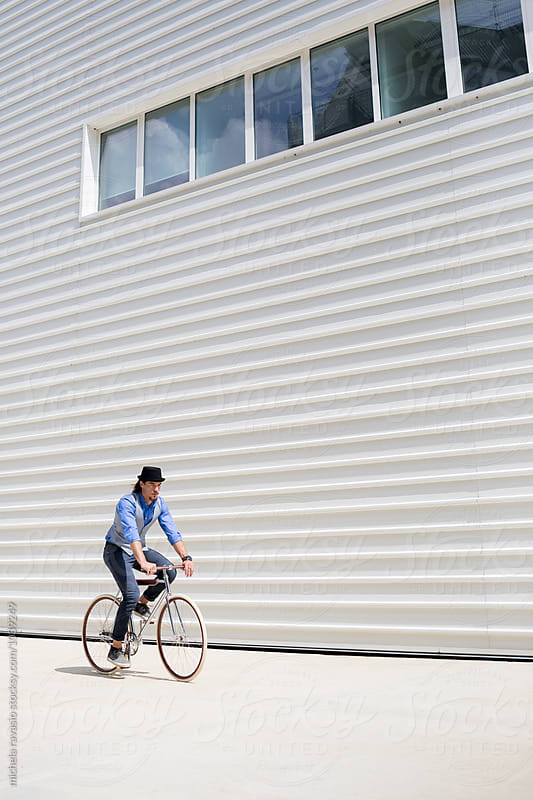 Young man cycling in urban area by michela ravasio for Stocksy United