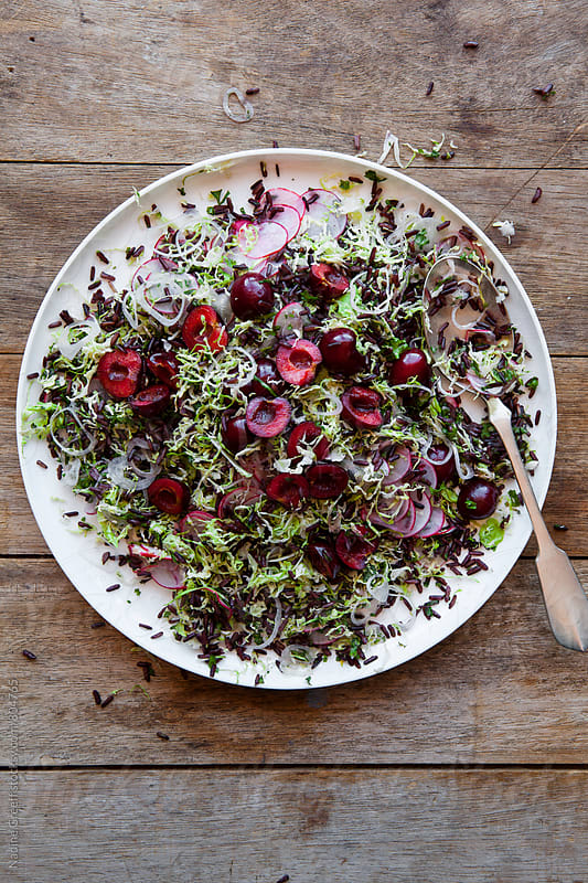 Grated brussel sprout salad with cherries, black rice, radish, onions and green herbs by Nadine Greeff for Stocksy United