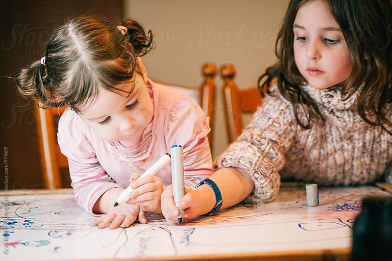 Two little girls colouring in together by Gary Radler Photography for Stocksy United