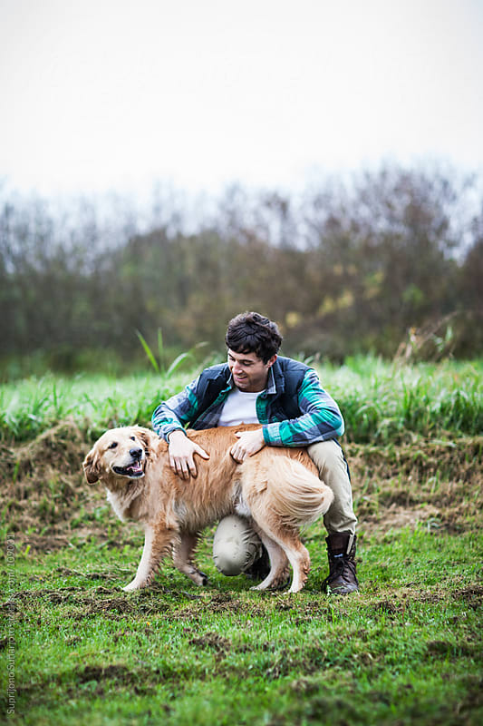 Man playing with his dog outdoor by Suprijono Suharjoto for Stocksy United