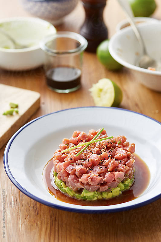 Tuna tartare in round shape on white plate with blue hem by Martí Sans for Stocksy United