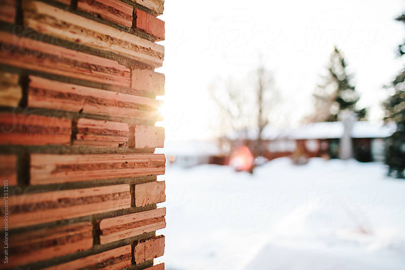 winter sunrise peeking past a brick wall by Sarah Lalone for Stocksy United