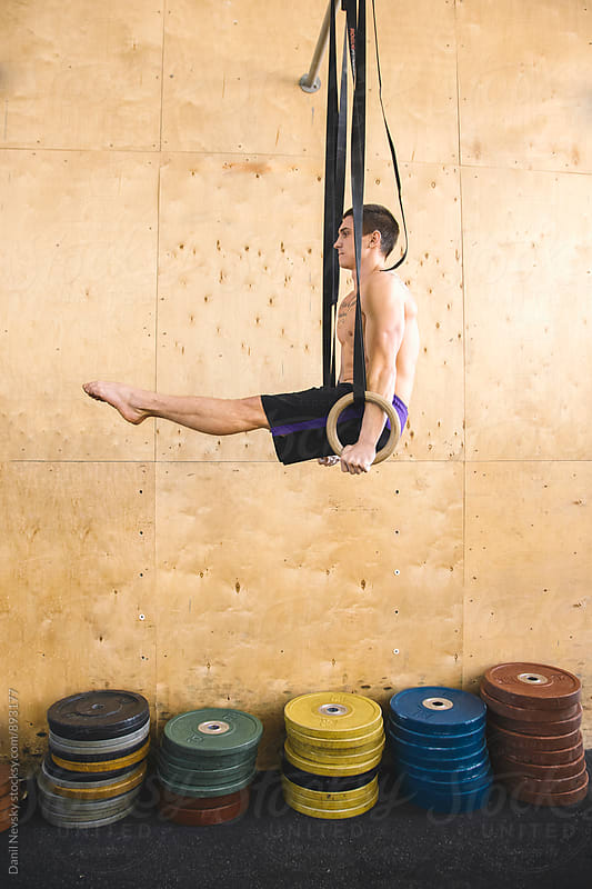 Young athlete performing gymnastic drill on rings by Danil Nevsky for Stocksy United