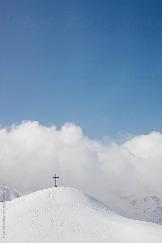 A cross on the top of a snowy mountain. by Koen Meershoek for Stocksy United