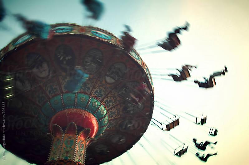 Blurry shot of a swing carousel ride at dusk by Carolyn Lagattuta for Stocksy United