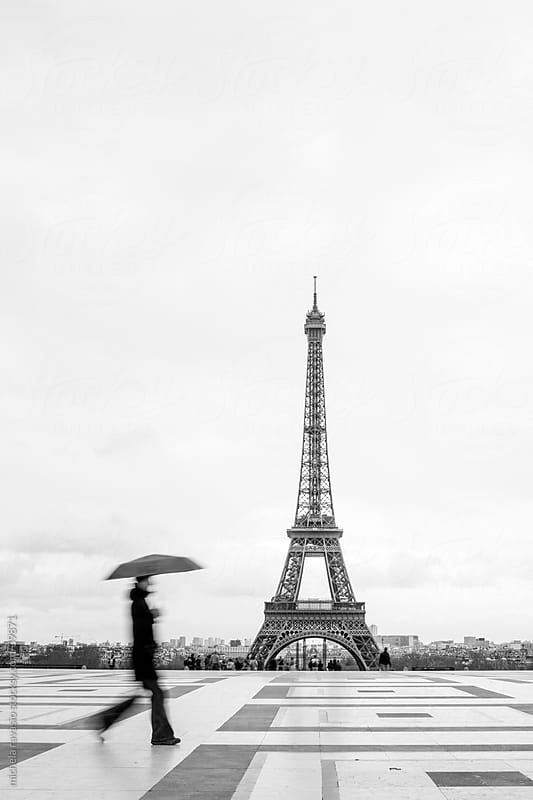 Woman with umbrella walking with the Eiffel tower in the background by michela ravasio for Stocksy United