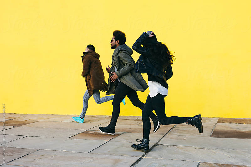 Side view of group of friends running in front of a yellow wall. by BONNINSTUDIO for Stocksy United