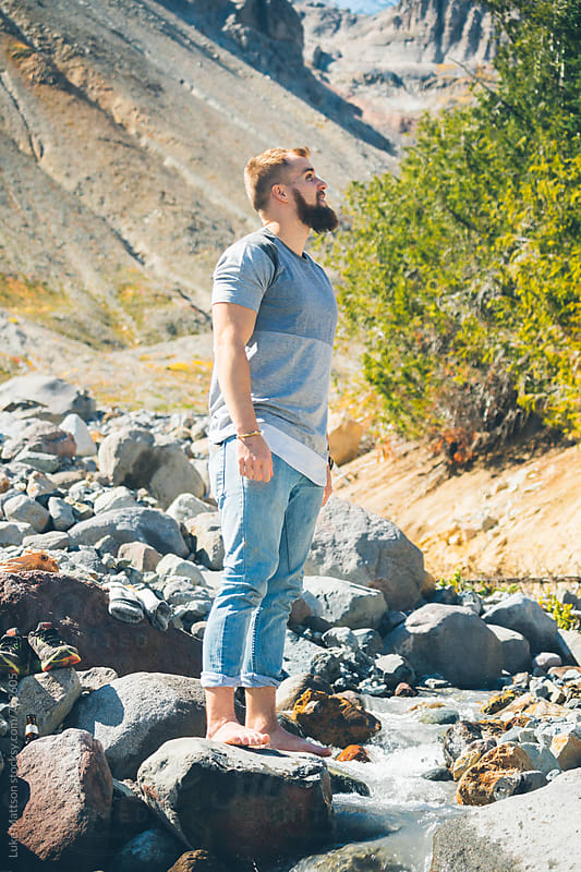 Blond Bearded Man Standing Barefoot On Boulder In Riverbed by Luke Mattson for Stocksy United