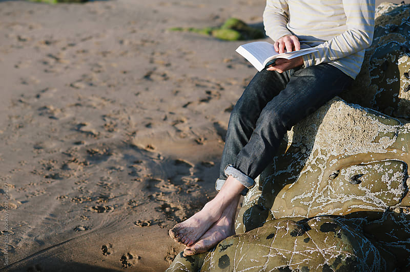 Man sits barefoot on a rock at the beach reading a book by Suzi Marshall for Stocksy United