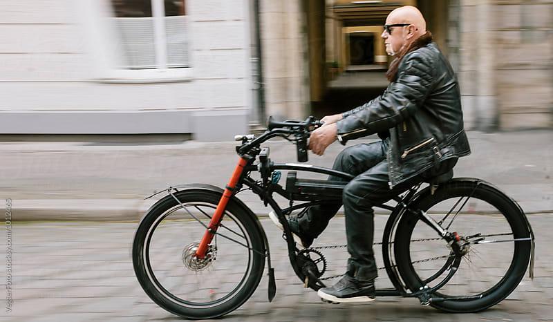 Senior adult riding E-Bike by VegterFoto for Stocksy United