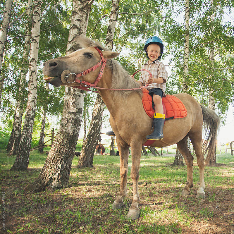 Smiling Boy Riding a Pony by Lumina for Stocksy United