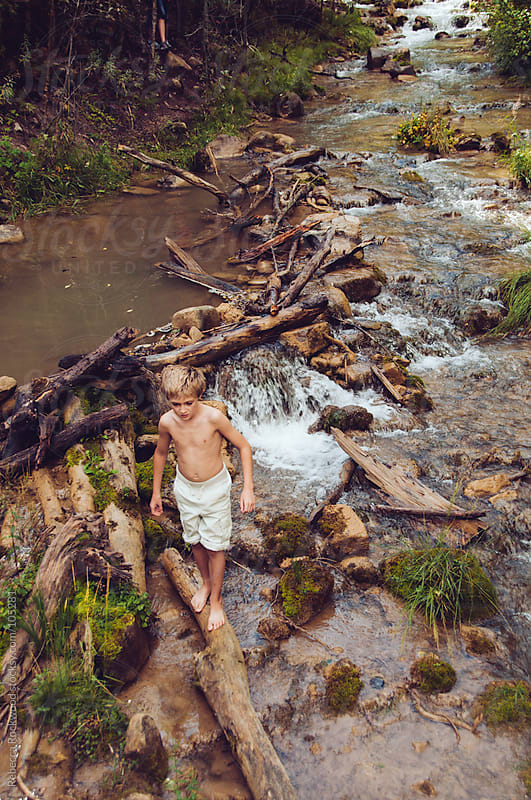 Young boy playing in a stream by Rebecca Rockwood for Stocksy United