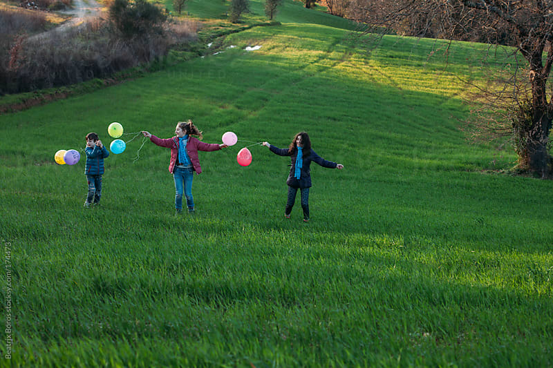 Kids playing with colorful ballons outdoors in the countryside by Beatrix Boros for Stocksy United
