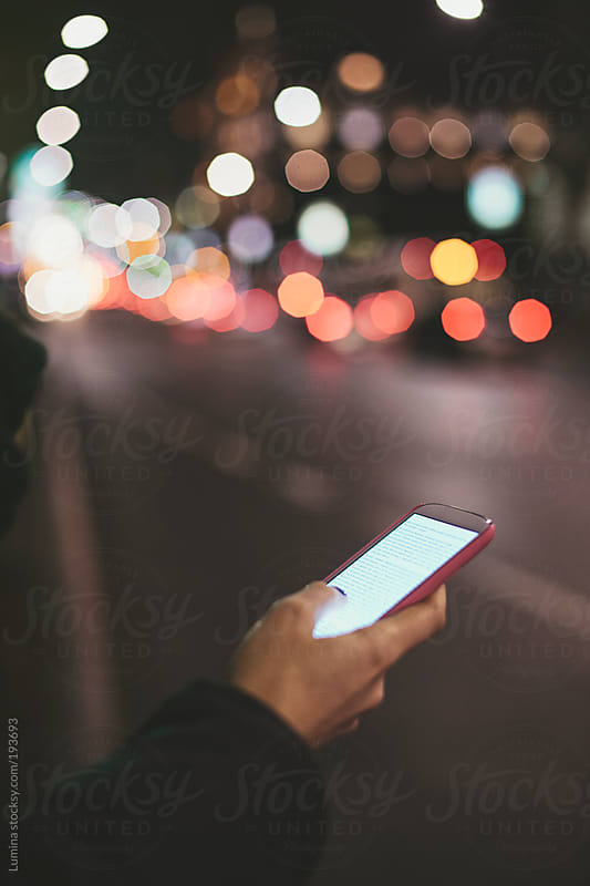 Woman Reading Text Messages on the Street by Lumina for Stocksy United