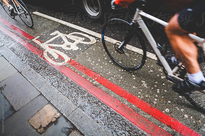 Cycling Commuter on Wet Bicycle Lane by Giorgio Magini for Stocksy United