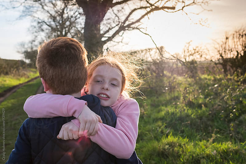 Brother and sister greeting each other with a hug. by Craig Holmes for Stocksy United