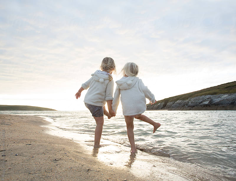 Two sisters (4 years old) playing in the sea.  by Hugh Sitton for Stocksy United