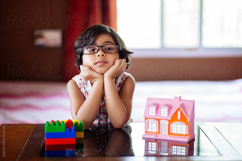 Little girl thinking deeply while playing with toy house by Saptak Ganguly for Stocksy United