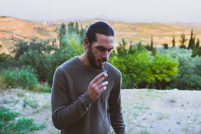 Male smoking in the countryside by María Barba for Stocksy United