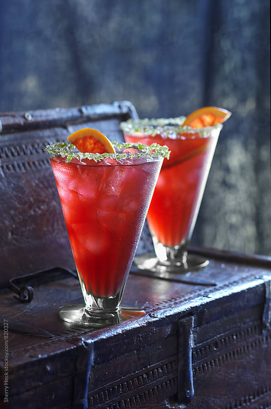 Red, icy drinks with herb and sugar rim on dark surface by Sherry Heck for Stocksy United