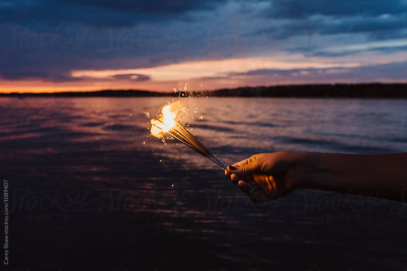 Bright sparklers against beautiful sunset  by Carey Shaw for Stocksy United