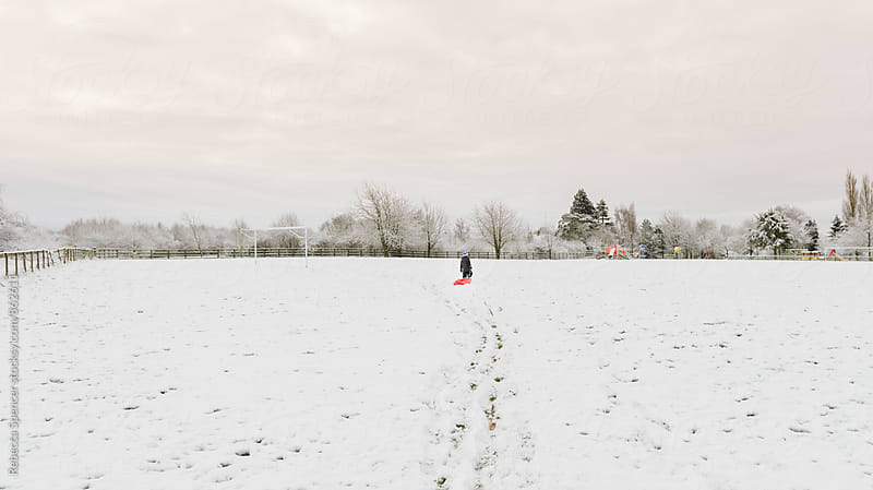 Child in the distance heads across a snowy English field to play park by Rebecca Spencer for Stocksy United