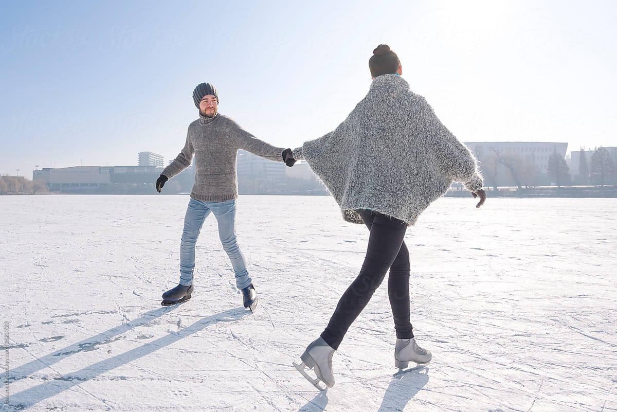Romantic couple ice skating outdoor on the frozen lake by RG&B Images for Stocksy United