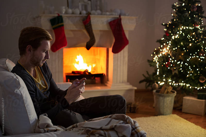 Caucasian Man Texting in a Christmas Setting by Lumina for Stocksy United