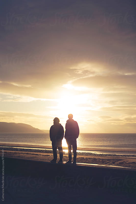 Father and son at sunset... by Catherine MacBride for Stocksy United