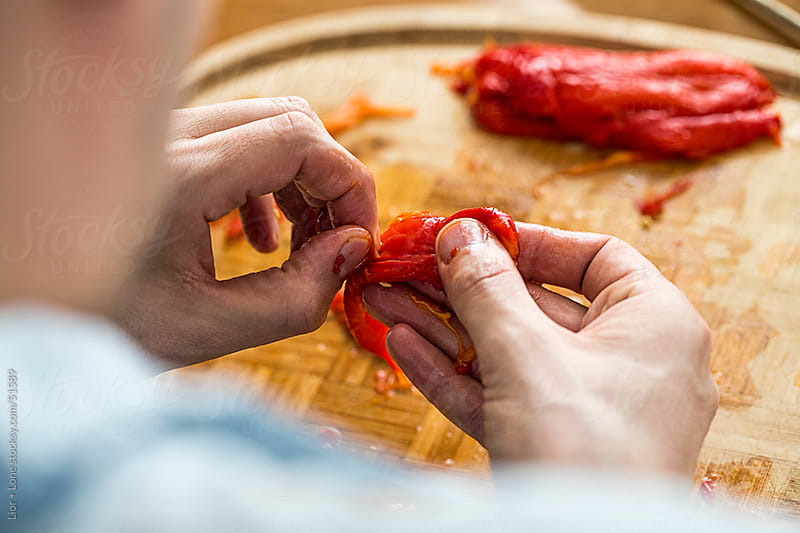 Man's hands peeling roasted peppers by Lior + Lone for Stocksy United