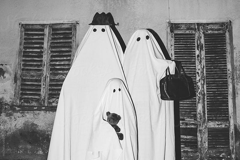 Family of ghosts in front of their home by michela ravasio for Stocksy United