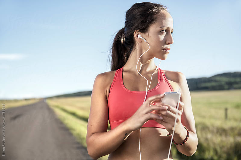 a fit woman holding a smartphone listening to music looking off camera by Shaun Robinson for Stocksy United