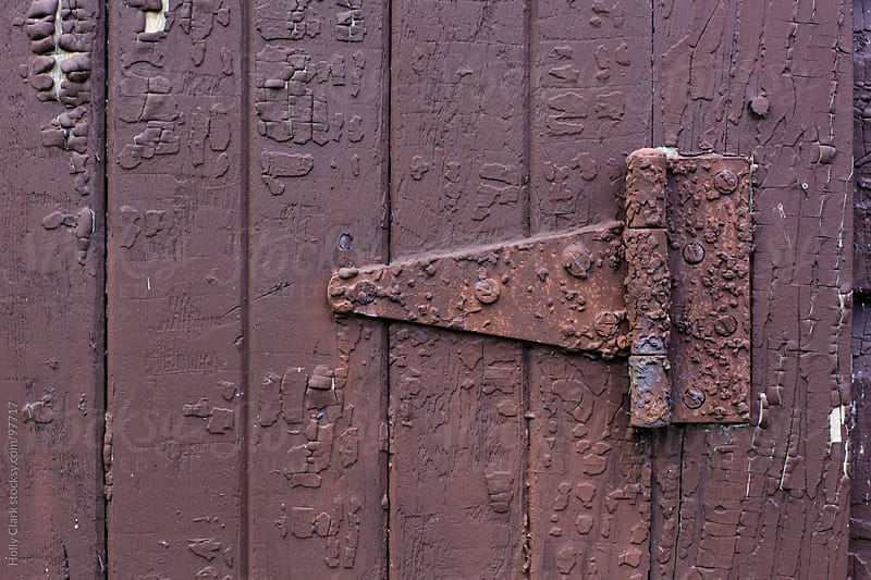 A rusty hinge on the side of a brown, wooden barn. by Holly Clark for Stocksy United