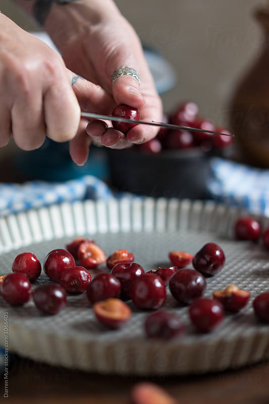 Preparing cherries for a recipe. by Darren Muir for Stocksy United