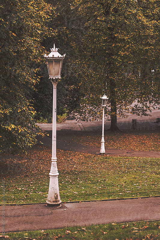 Two vintage white lampposts on urban park. by BONNINSTUDIO for Stocksy United