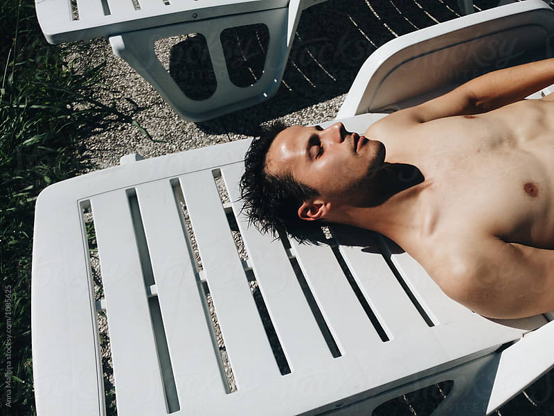 A young man sunbathes on the sun by Anna Malgina for Stocksy United